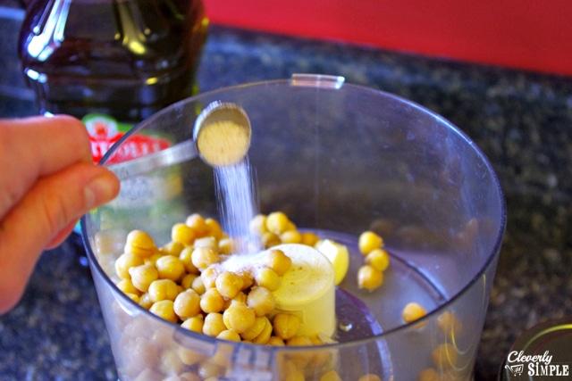 adding salt to taste to make homemade hummus with garlic