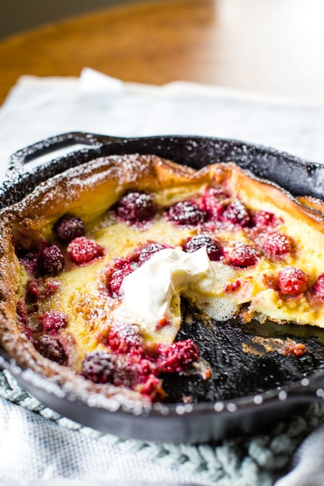 german pancakes with berries in cast iron skillet