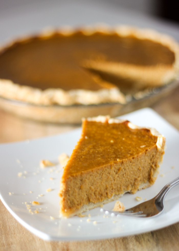 pumpkin pie on plate with pie in background