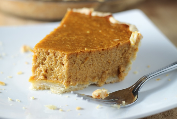slice of pumpkin pie with bit taken out of it