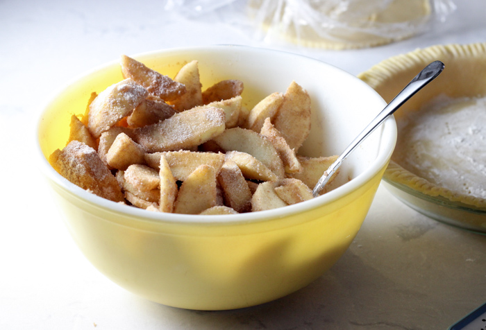 peeled apples in bowl with cinnamon and sugar