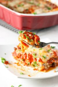 classic lasagna on plate with fork holding bite