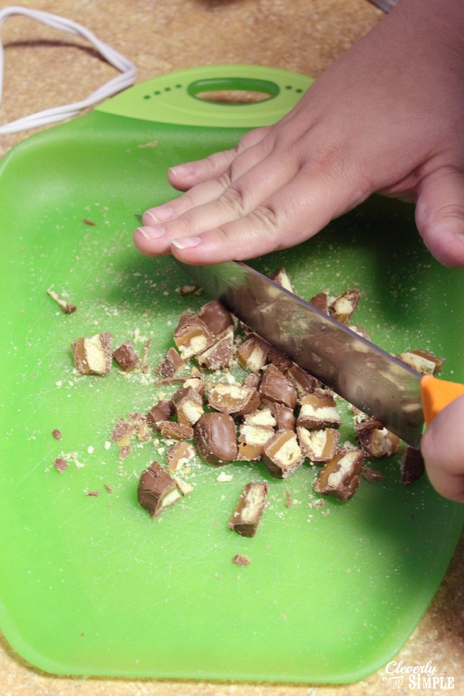 Cutting up Twix Candy in homemade fudge recipe