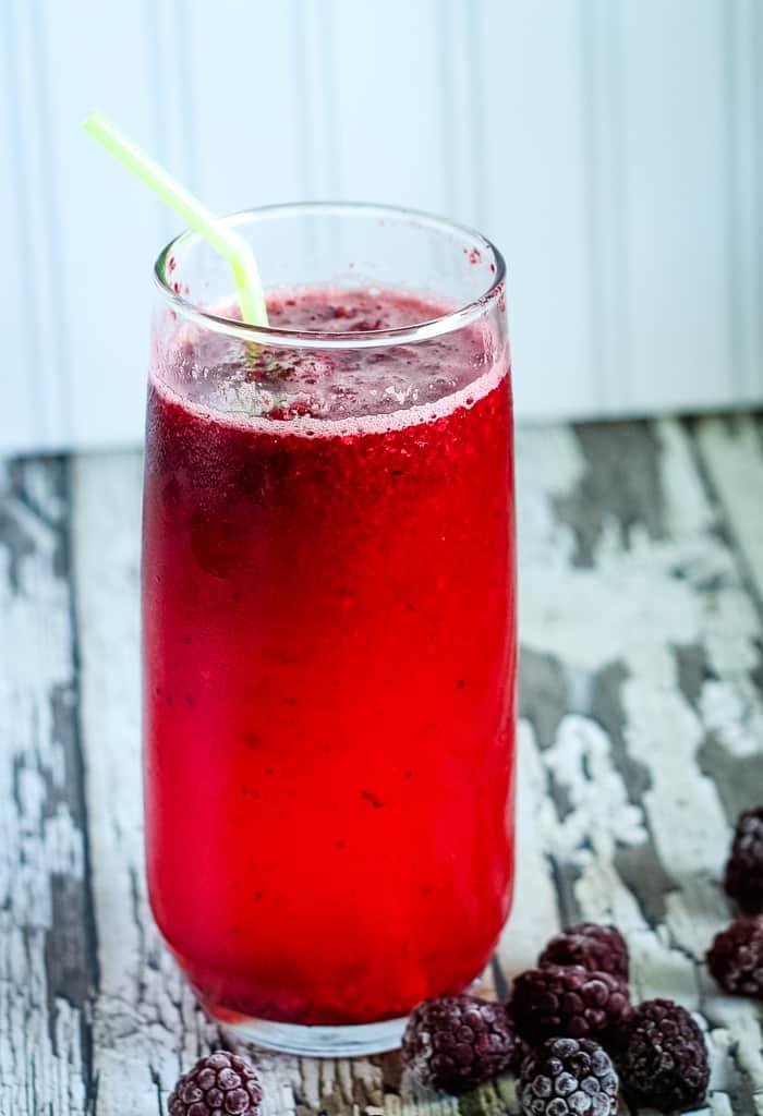 homemade blackberry lemonade in glass with straw
