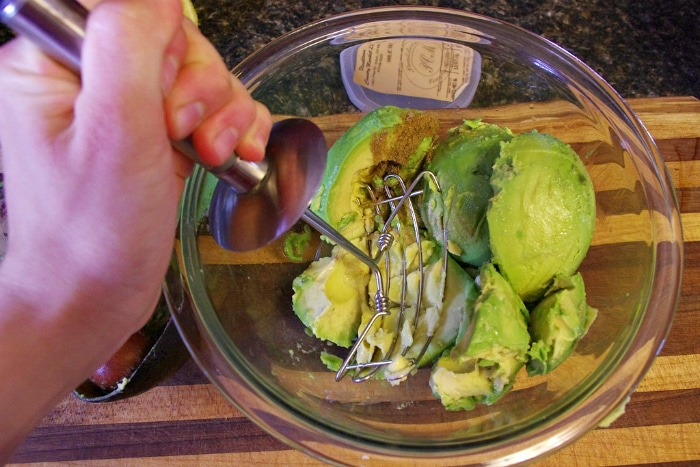 Smashing up the avocados for basic guacamole