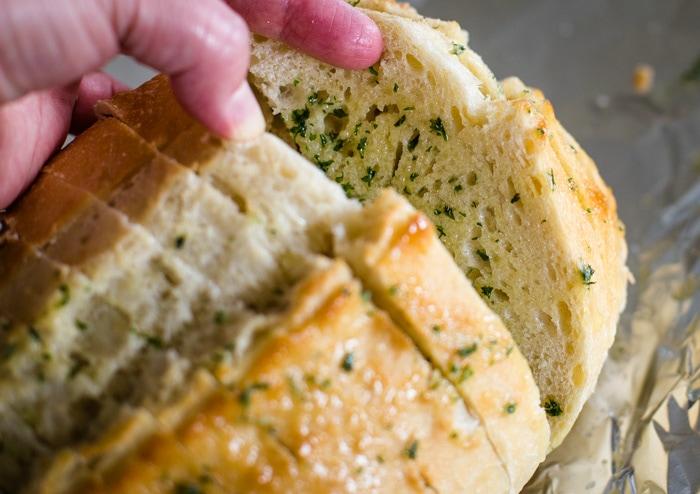 adding garlic powder, butter and dried parsley to make garlic bread