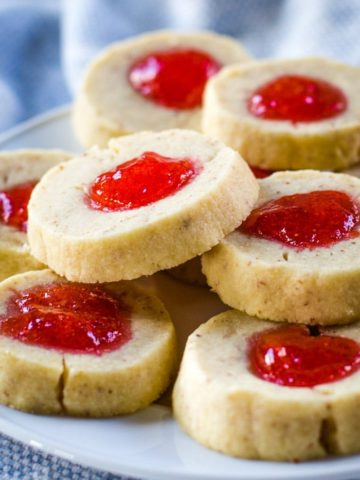 almond thumbprint cookies with strawberry jelly on plate