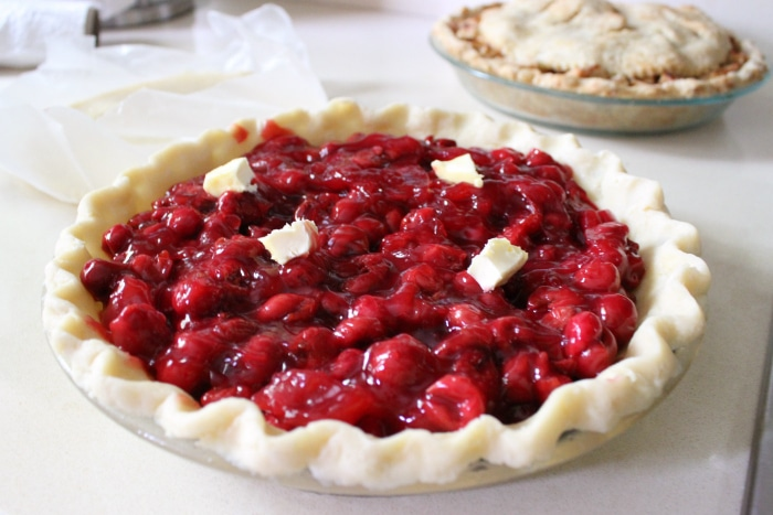 four pats of butter on the cherry pie filling in a pie crust