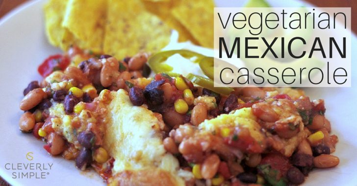 baked mexican casserole on a plate with tortilla chips avocado and peppers