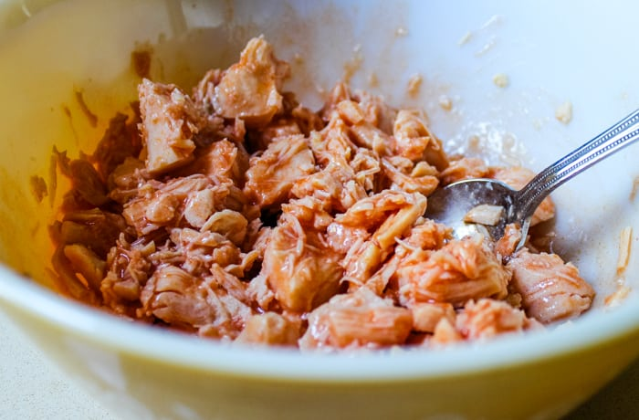 chicken and buffalo sauce mixed in bowl for baked buffalo chicken dip