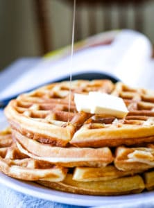waffle stack on plate with drizzle of syrup and butter