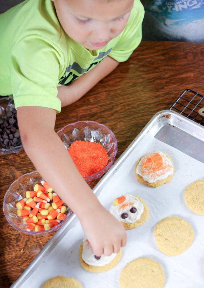 boy decorating pumpkin cookies with candy corn sprinkles and chocolate chips