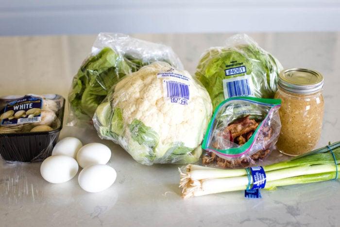 ingredients to make salad, cauliflower, bacon, bibb lettuce, green onions, eggs and mushrooms