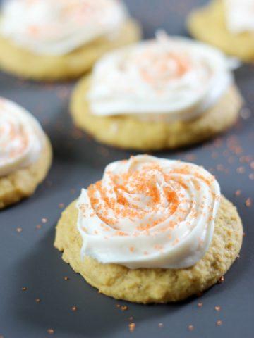 pumpkin cookies with cream cheese icing on dark background