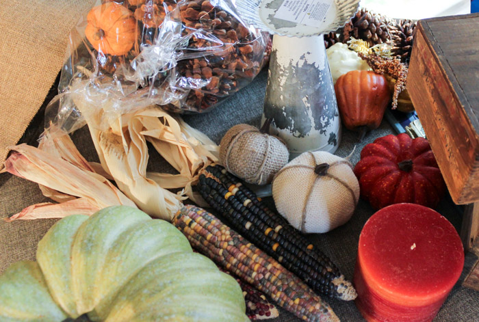 fall decorations including pumpkins, harvest corn, candles, pinecones and rustic candle holder