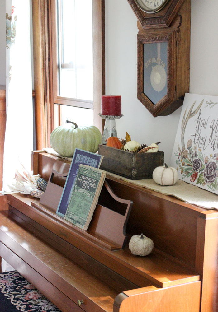 piano decorated for fall with antique music, candles, rustic candlestick, pumpkins and gourds