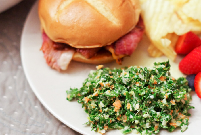 kale salad on plate with chips and sandwich