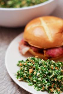 kale salad recipe made on plate with ham sandwich