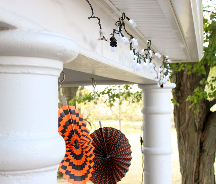 porch with ghost twinkle lights and orange and black fans