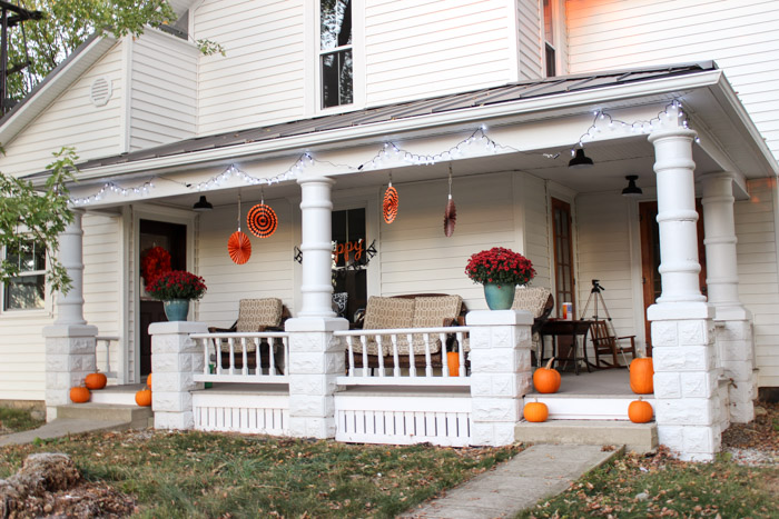 fall porch decor with pumpkins mums twinkle lights