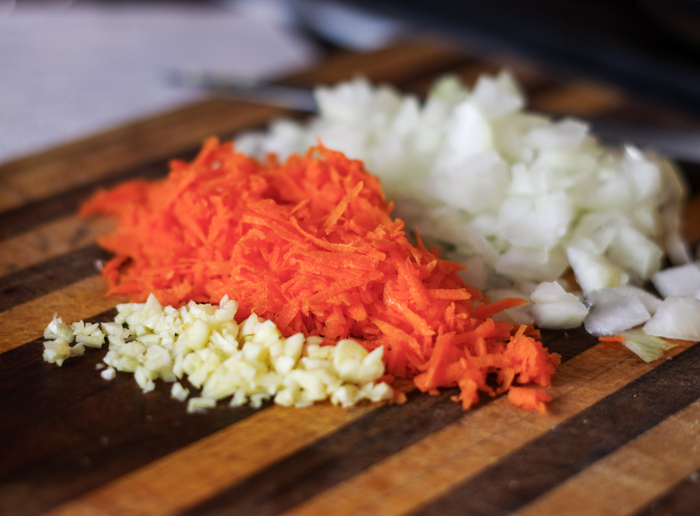 cutting board with chopped carrots, onion and garlic