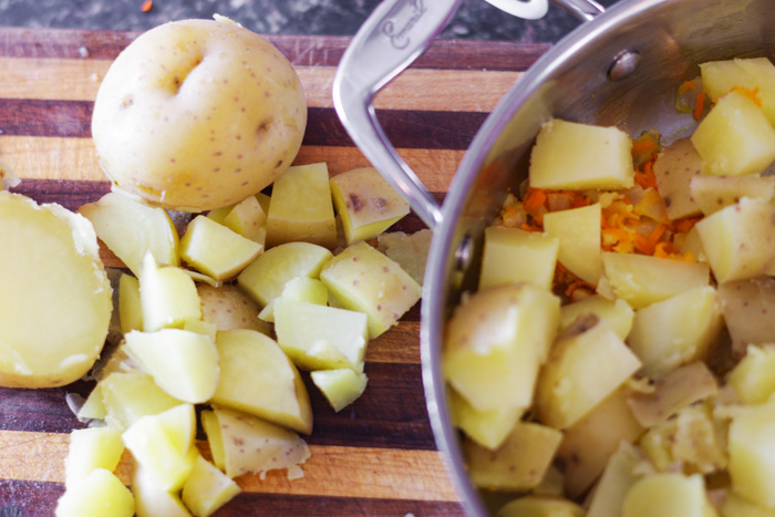 cooked potatoes being sliced for pan