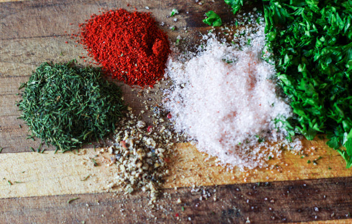 cutting board with parsley, salt and other spices
