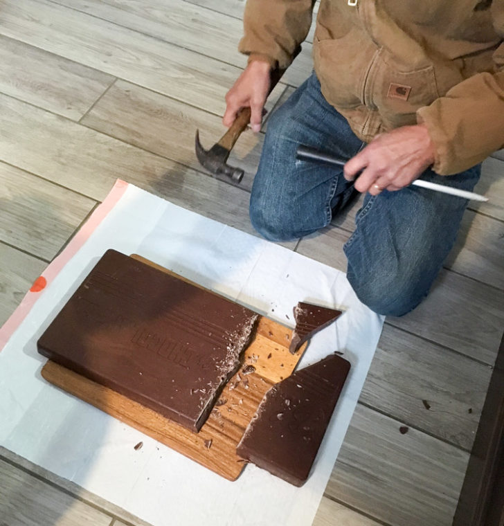large chocolate bar being split by hand