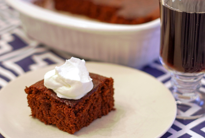 molasses cake with whipped cream on plate with cup of coffee