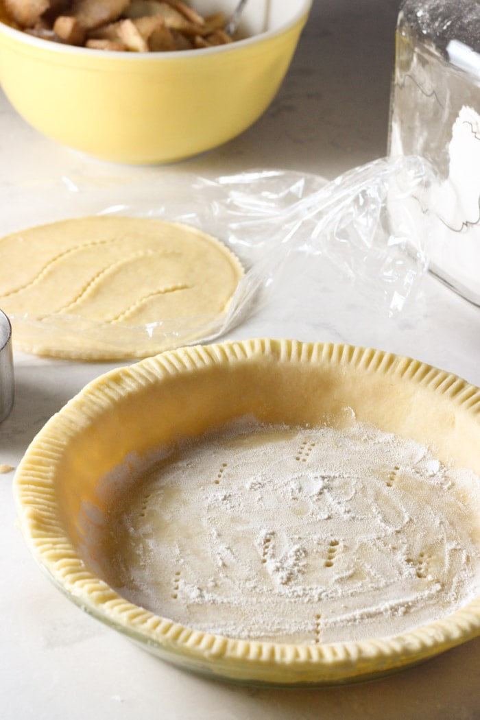 pie crust with topper and bowl of apples