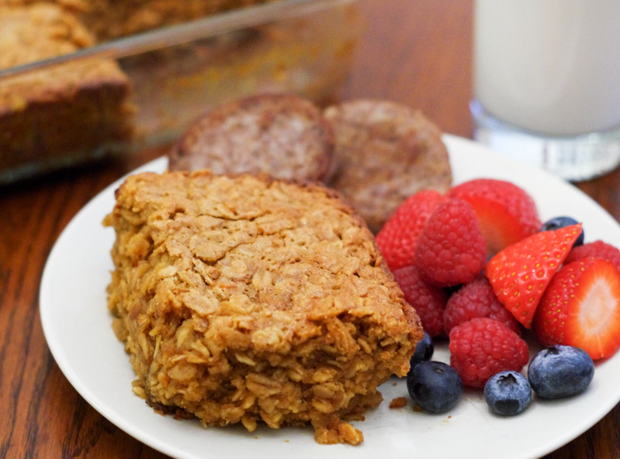 baked oats on plate with fruit sausage and glass of milk
