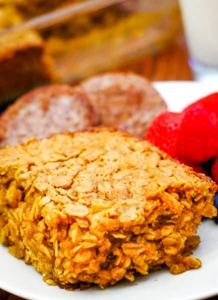 baked oatmeal on white plate with fruit and sausage