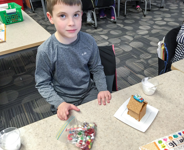 child with gingerbread house at school desk