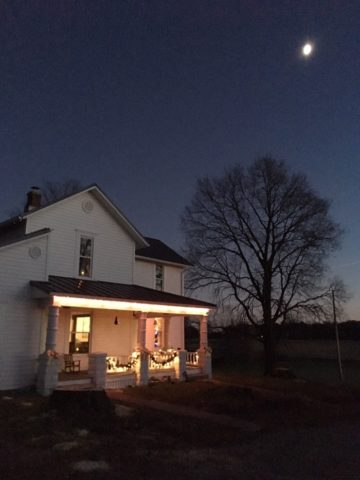 farmhouse at night with moon and Christmas lights