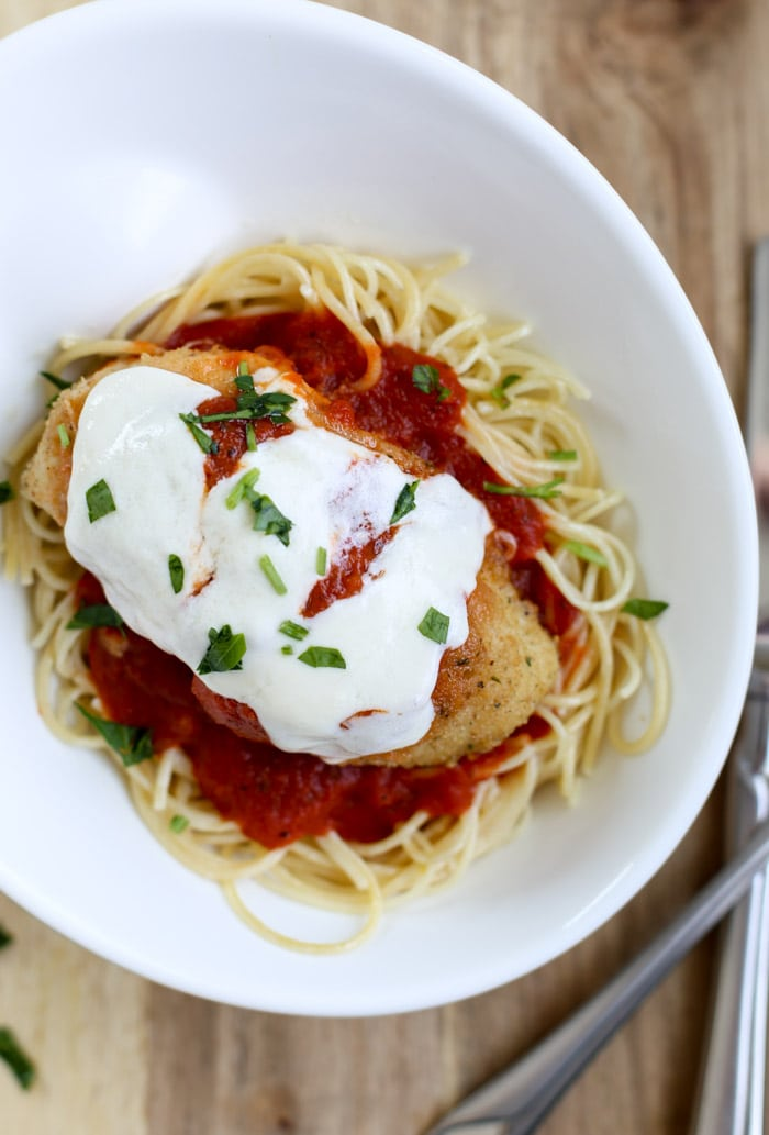 chicken parmesan on pasta on plate with silverware