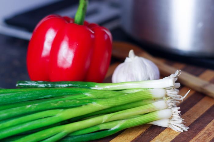 green onions garlic and pepper on cutting board