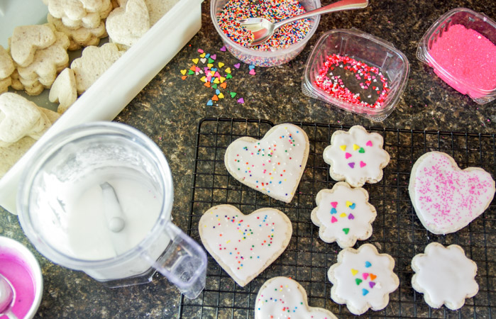 sugar cookies with icing on cooling rack with sprinkles