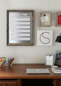 desk with magnetic calendar and frames on wall
