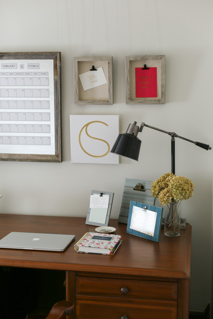 side of desk with lamp and frames