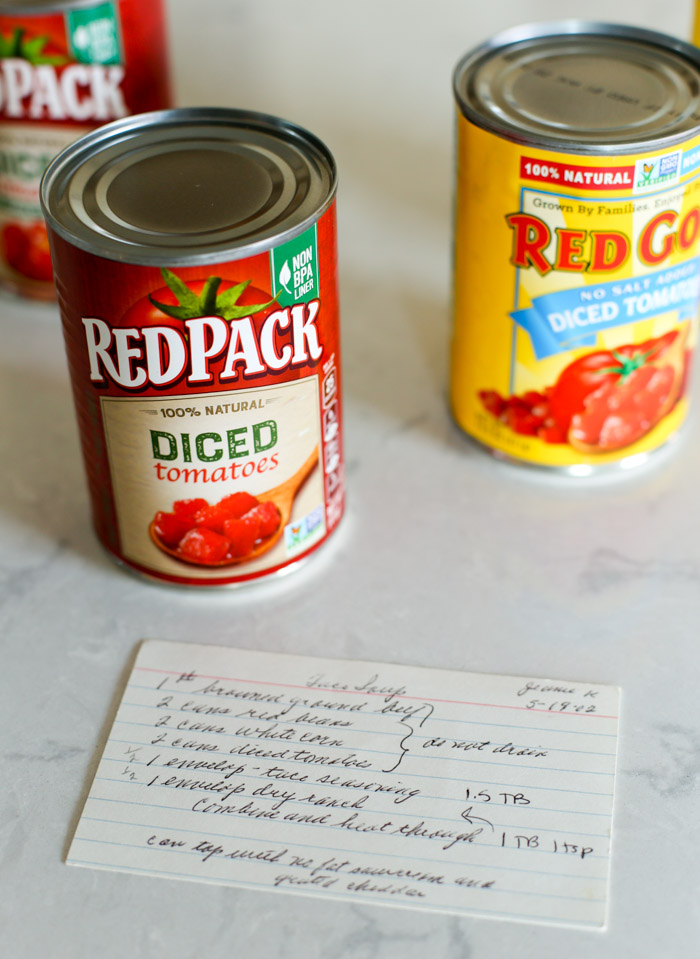 recipe card on countertop with cans of diced tomatoes