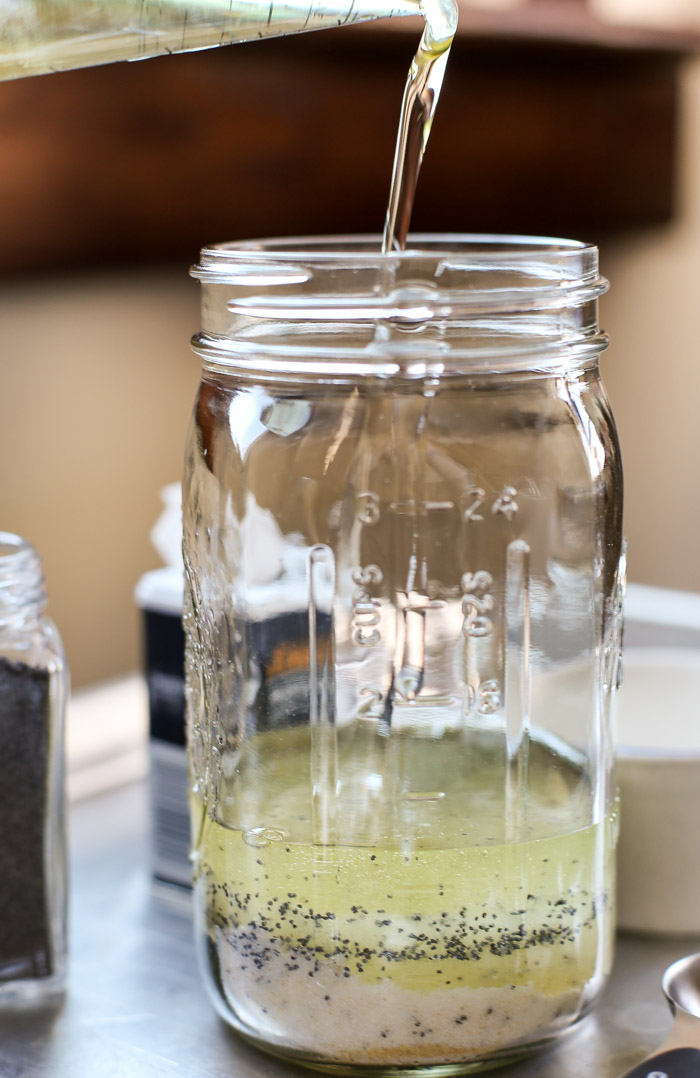 pouring vegetable oil into mason jar with ingredients