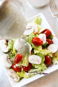 pouring poppyseed dressing on salad in bowl