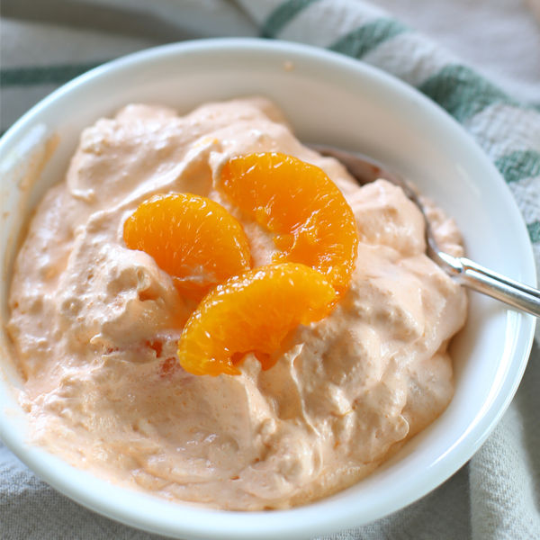 orange fluff salad in bow with spoon