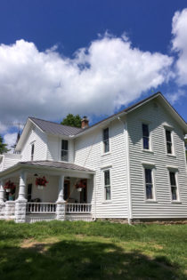 white farmhouse in Ohio on hill