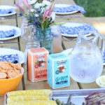 picnic table with food and flowers for outdoor entertaining