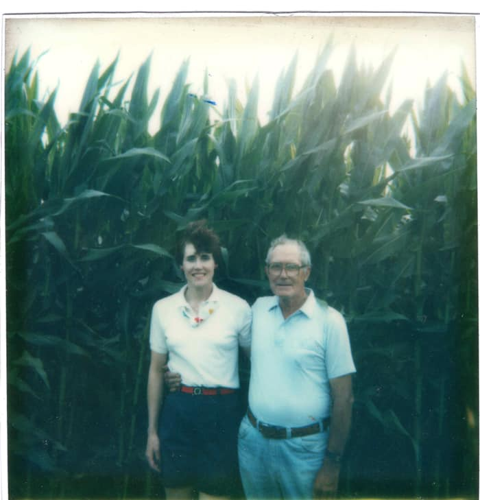 daughter and dad in front of corn field