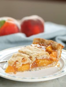 peach pie on plate with peaches
