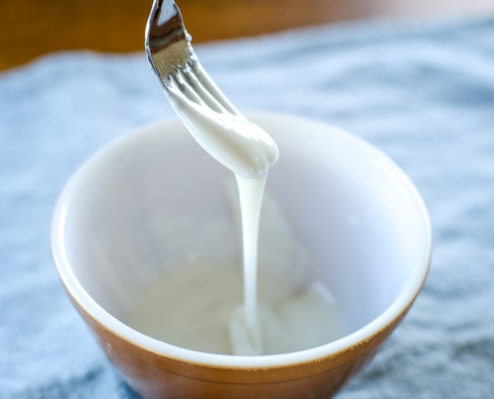 powdered sugar and milk mixed in a bowl with fork