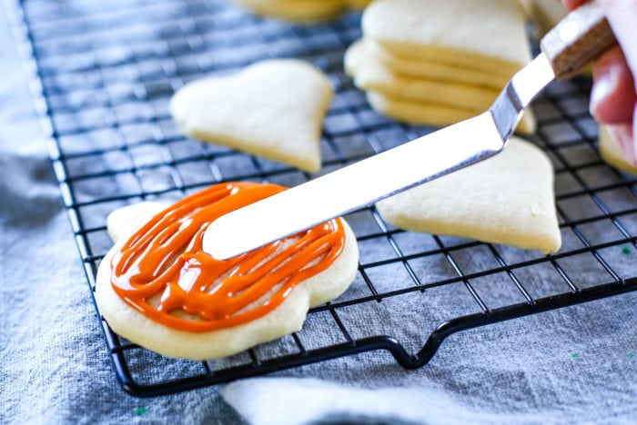 using knife to spread icing on cookie