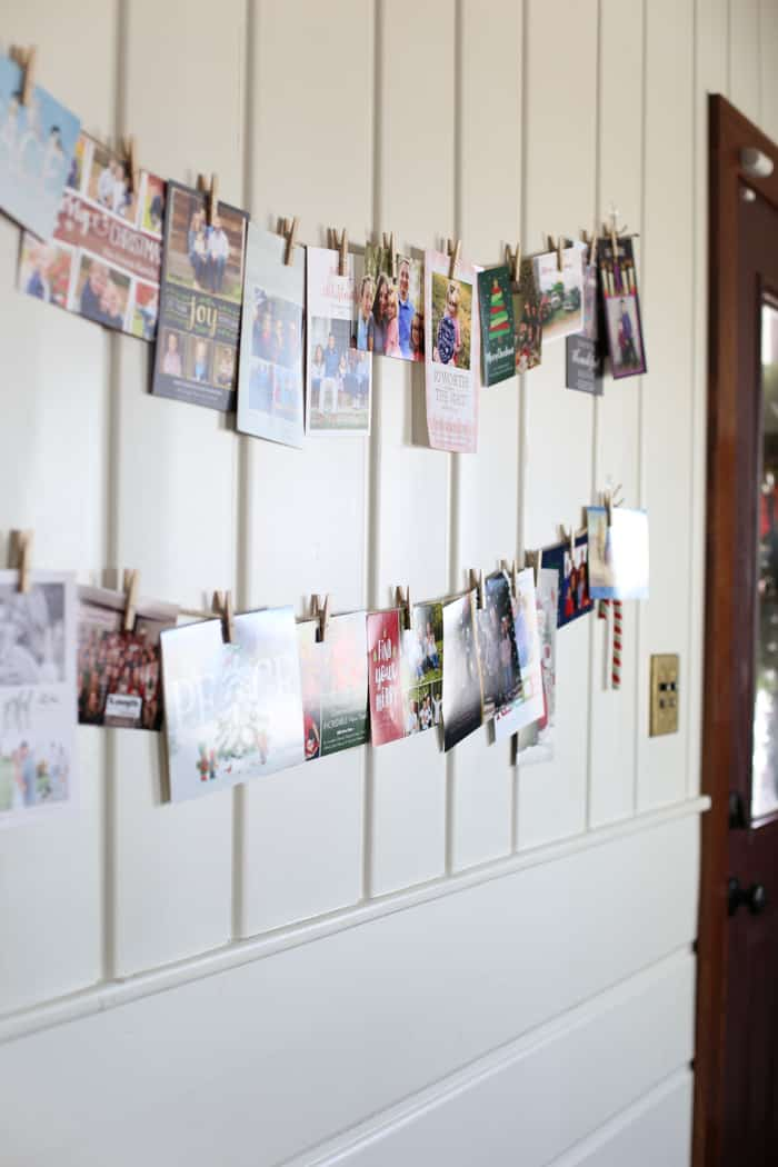 DIY homemade Christmas card holder that is the perfect display using twine, command hooks and clothespins. Removable, customizable and festive! #christmasdecor #christmascards